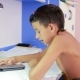 Teenage Boy Doing Homework Using a Cell Phone. Natural Video