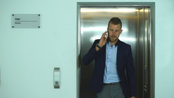Download Business Businessman Steps Out Of The Elevator And Talking On The Phone nulled download