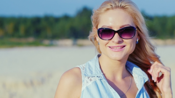 Download Sexy Blonde Woman In Sunglasses, Posing For The Camera At The Beach nulled download