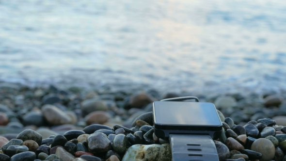 Download Blurred Smart Watches Are Near The Pebble Beach Of The Ocean. The Clock Reflects The Sky Clouds. . nulled download