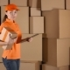 Beautiful Female Courier In Orange Uniform Delivering a Parcel Against Carton Stacks Backround