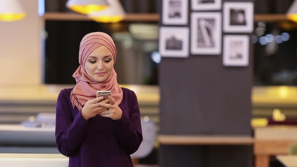 Download Beautiful Muslim Girl Uses Smartphone In Cafe nulled download