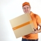Delivery Man In Orange Uniform Throwing a Big Parcel At The Camera. Light Gray Backround,  Studio