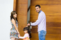 Adorable hispanic family of three posing for camera outside front entrance door while entering house