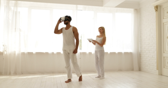 Download Man Using a Virtual Reality Glasses and the Woman is Holding a Digital Tablet  nulled download