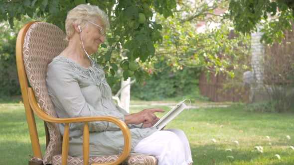 Download Elderly Woman Switches The Music On The Tablet. nulled download