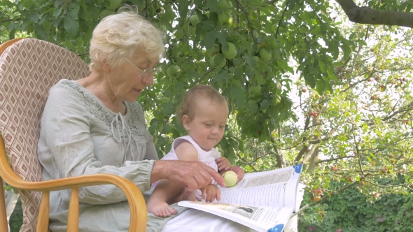Download Grandma Reading a Book To Her Granddaughter. nulled download