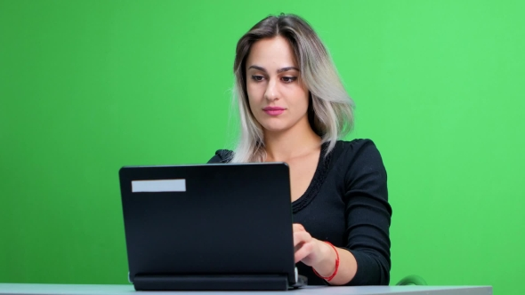 Download Girl Sitting At The Table And Working At a Laptop. Green Screen Studio nulled download
