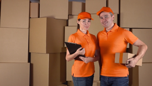 Download Male Anf Female Couriers In Orange Uniform Standing Against Brown Cardboard Boxes Backround nulled download