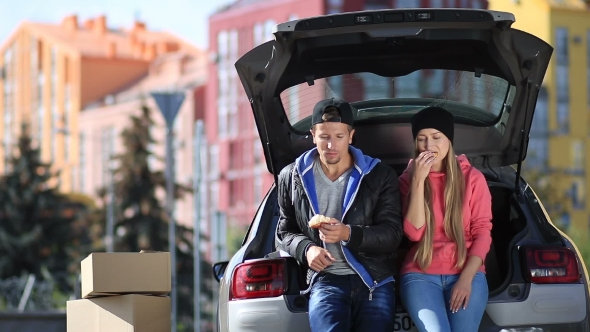 Download Smiling Couple Sitting In Trunk Of Modern Car nulled download