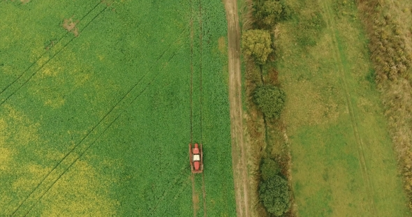Download Tractor Spray Green Crop Field Near Village Houses In Autumn nulled download