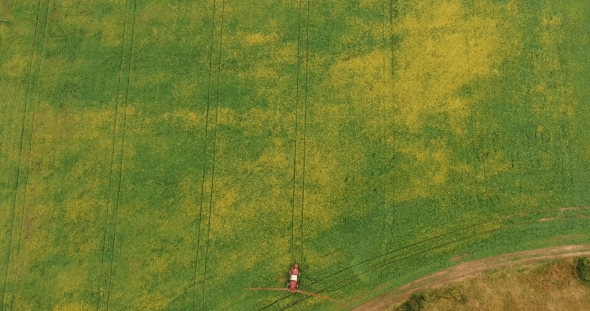 Download Aerial Shot Tractor Sprayers Lays on the Field With a Canola nulled download