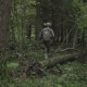 Soldiers Go Through The Woods. Military With Arms Sent To The Thickets Of Green. Airsoft Game