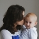 Young Happy Mother Holding Her Newborn Child. Family At Home. Beautiful Smiling Mom And Happy Baby