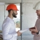 Two Builders Looking At The Digital Tablet At The Building Under Construction
