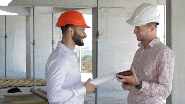 Download Two Builders Looking At The Digital Tablet At The Building Under Construction nulled download