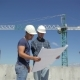 Construction Manager Points At The Plan Of Building Under Construction