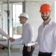Male Builder Holds Set Of Plans Of Building Under Construction