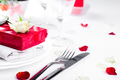 Elegant holiday table setting with red ribbon gift