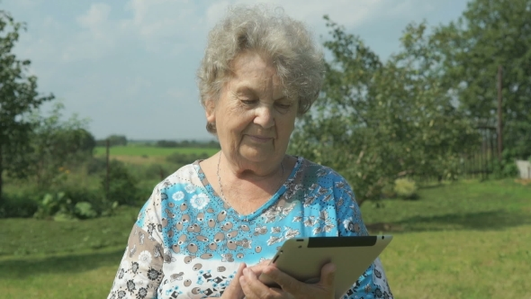 Download Elderly Woman Walking With Digital Tablet Outdoors nulled download