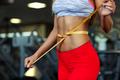 Woman measuring perfect shape of beautiful waist