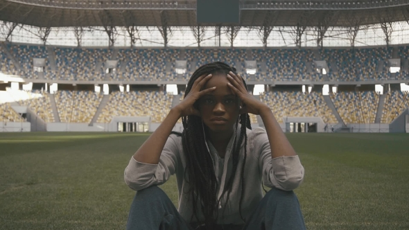 Download Nervous Sporty African-american Woman Sitting Alone In The Middle Og Sports Stadium And Looking To nulled download