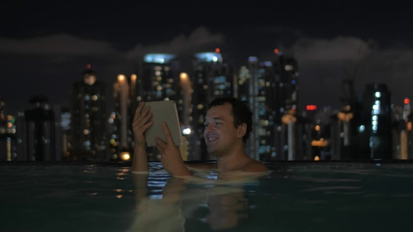 Download Man With Pad In Rooftop Pool Of Night Kuala Lumpur nulled download