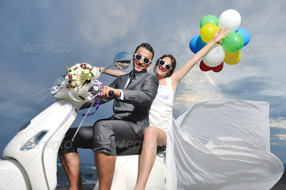 Stock Photo - PhotoDune just married couple on the beach ride white scooter 1795549