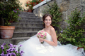 Beauty bride in bridal gown with bouquet on the nature