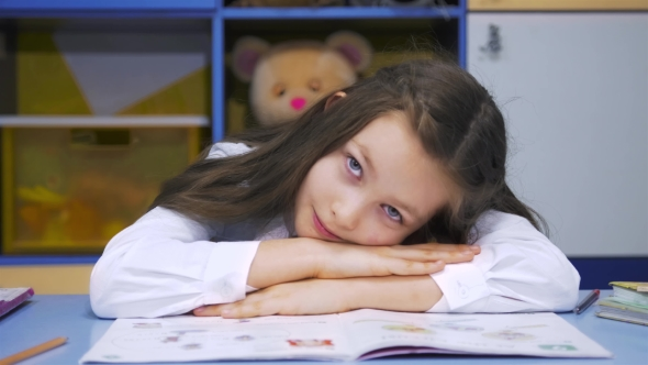 Download Cute Little Girl Studying At The Library Doing Homework And Smiling nulled download