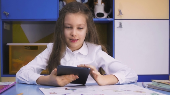Download Cute Little Girl Studying At The Library Doing Homework With Tablet nulled download