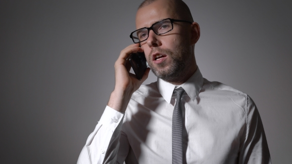 Download Businessman Leads a Serious Conversation With a Colleague On The Phone. nulled download