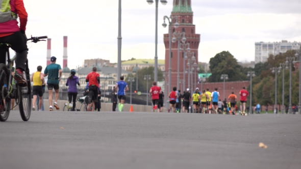 Download Unrecognizable Marathon Runners And Cyclists Against Moscow Kremlin.  Background Bokeh Long Shot nulled download