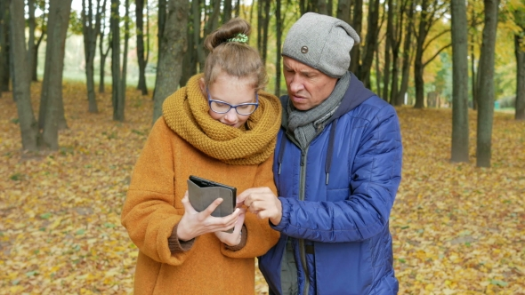 Download Daughter Teenager Teaches His Father To Work With The Tablet In The Autumn Park. Dad Listens nulled download