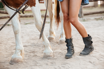 Legs of woman and horse walking together on ranch