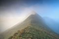 mountain peak in dense fog