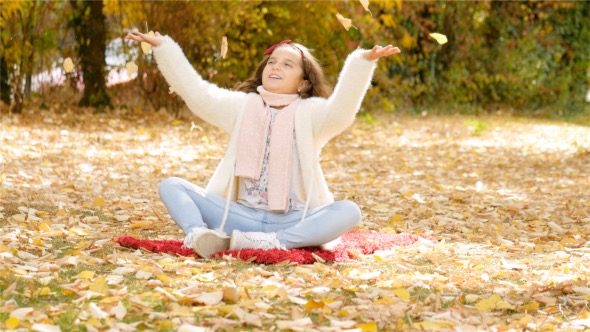 Download Child Playing With Leaves in Autumn nulled download