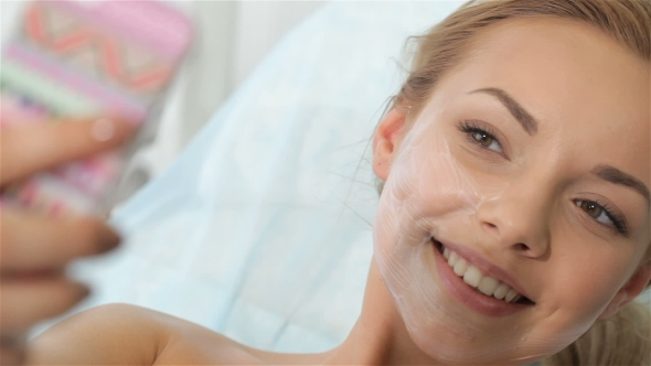 Download Girl Looks At Her Smartphone With Cosmetic Mask On Her Face nulled download