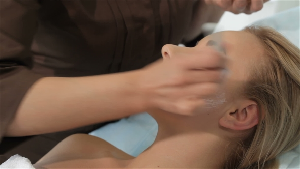 Download Female Cosmetologist Smears Cosmetic Treatment On Client's Face nulled download