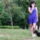 Young Woman Having Fun With Dachshund Dog In Park Talking On The Phone.