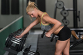 Young Woman Doing Back Exercise With Dumbbells