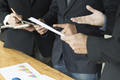 businessman analyzing and discussing with tablet and paperwork d