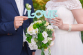 bride and groom holding wooden word love