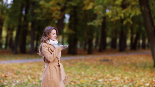Download Woman With Smartphone Walking In Autumn Park 3 nulled download