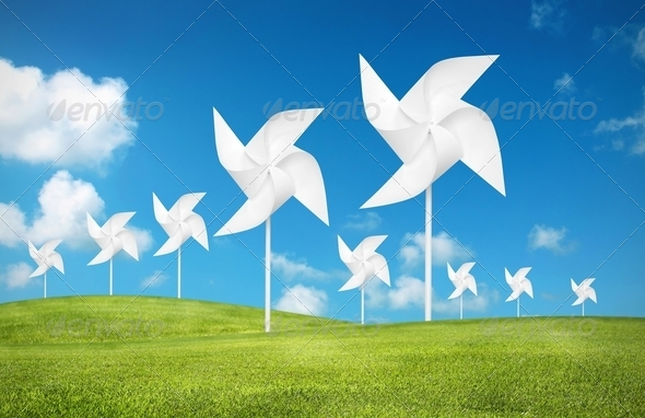 paper toy windmill in green grass field - Stock Photo - Images