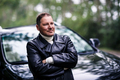 Businessman in leather jacket standing near car
