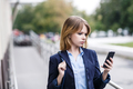 Businesswoman using smartphone outdoors,