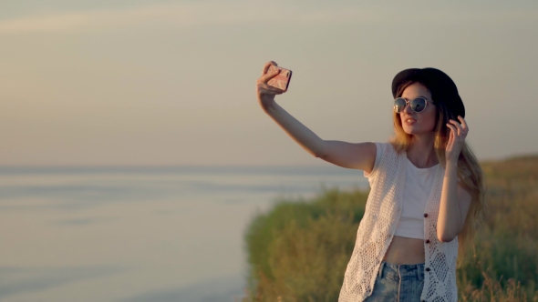 Download Young Woman Making Selfie On The Edge Of a Cliff Near The River nulled download