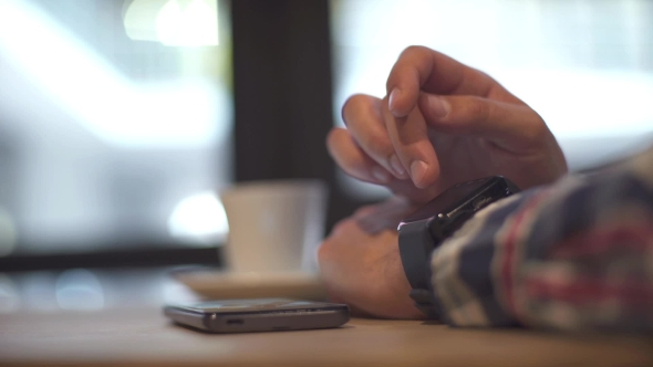 Download In Coffee Bar a Man Using His Smartwatch.  Hands nulled download
