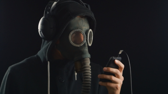 Download Man Listens To Music With Headphones With a Gas Mask Covering His Face. nulled download
